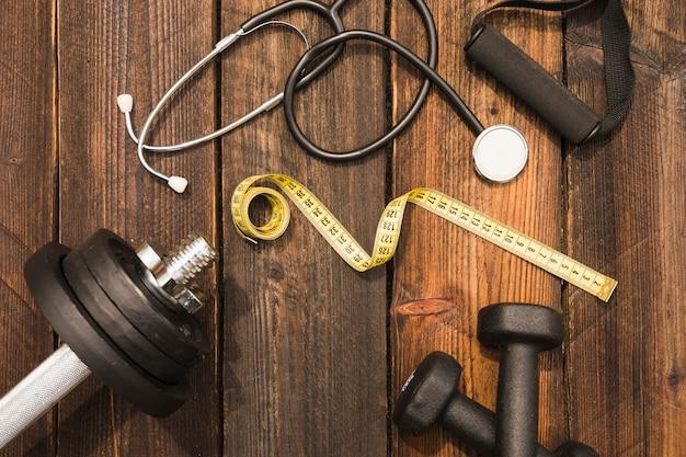 Eignungsausrüstung mit stethoskop und messendes band auf holzoberfläche Kostenlose Fotos