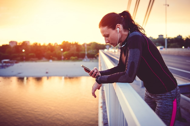 Eignungsfrau, die intelligentes telefon verwendet Premium Fotos