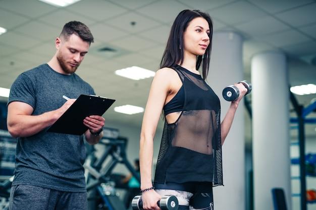 Eignungsfrau, die mit eignungstrainer in der turnhalle trainiert. Premium Fotos