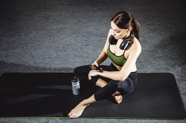 Eignungsfrau, die nach training in der turnhalle stillsteht Premium Fotos