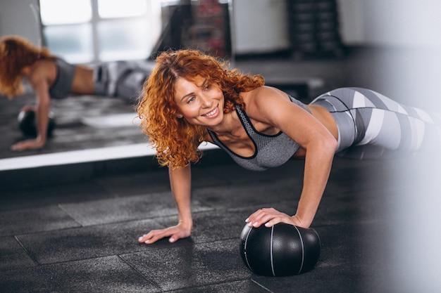 Eignungsfrau, die push-ups an der turnhalle tut Kostenlose Fotos