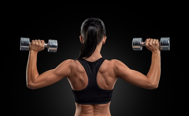 Eignungsfrau in den trainingsmuskeln des rückens mit dummköpfen Premium Fotos