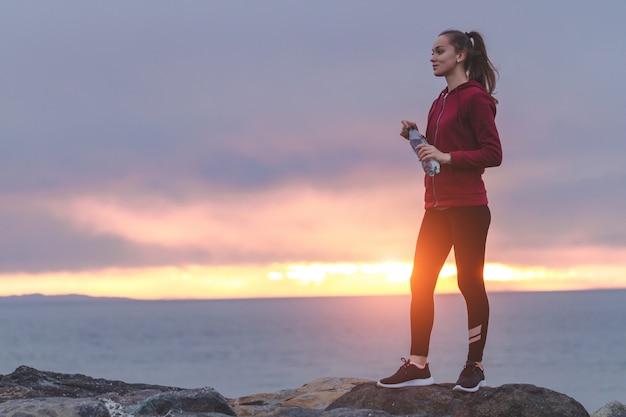 Eignungsfrau in den turnschuhen, die auf einem stein stehen, eine flasche wasser halten und den abstand nach einem training auf einem seehintergrund sonnenuntergang untersuchen Premium Fotos