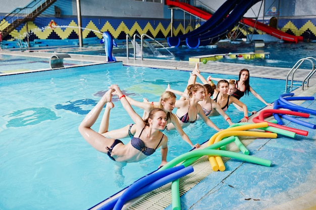 Eignungsgruppe mädchen, die aerobic-übungen im swimmingpool am aquapark tun. Premium Fotos