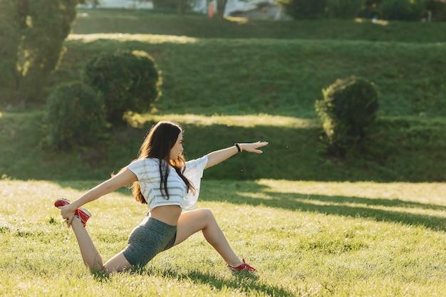 Eignungsmädchen, das draußen ausdehnende übungen auf sonnenschein ein gras macht Premium Fotos