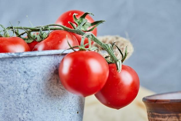 Eimer mit roten saftigen tomaten auf holztisch. Kostenlose Fotos