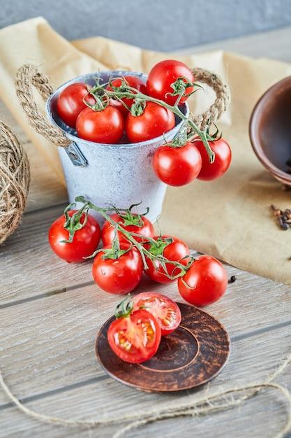 Eimer mit tomaten und halb geschnittenen tomaten auf holztisch. Kostenlose Fotos