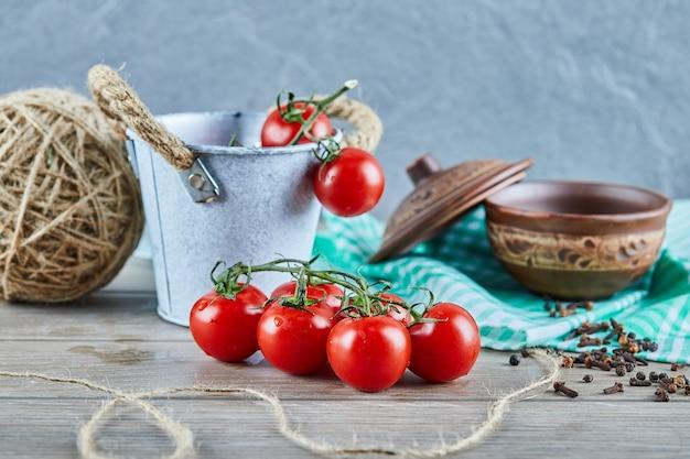 Eimer mit tomaten und nelken auf holztisch mit leerer schüssel Kostenlose Fotos
