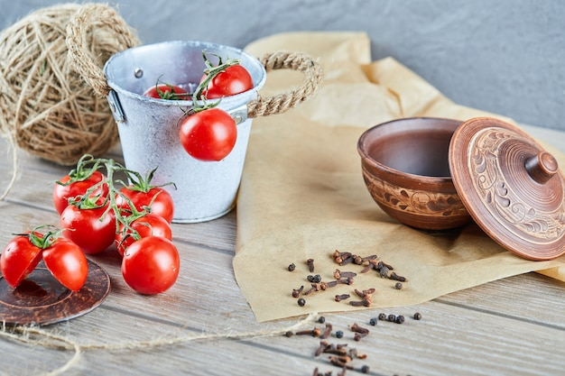 Eimer tomaten und halb geschnittene tomate auf holztisch mit leerer schüssel Kostenlose Fotos
