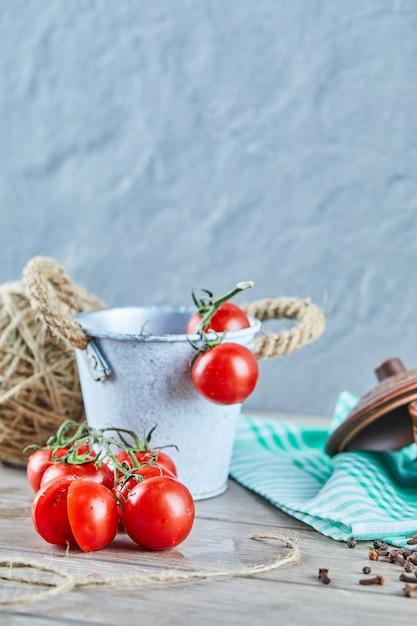 Eimer tomaten und halb geschnittene tomate auf holztisch Kostenlose Fotos