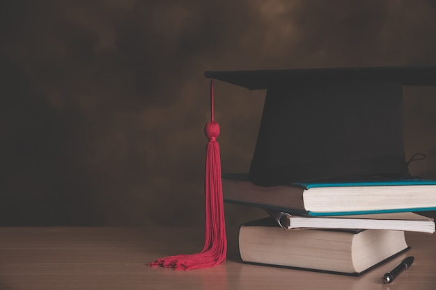 Ein abschluss doktorhut auf einen stapel bücher, mit pergamentrolle in roter schleife gebunden. Premium Fotos