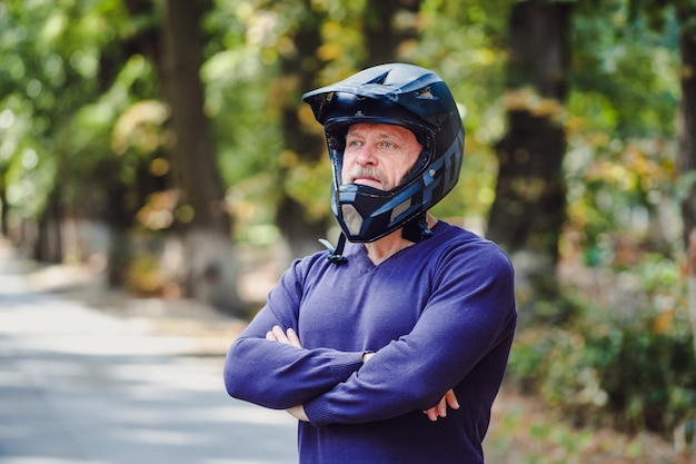 Ein älterer mann im dunklen sturzhelm im freien. freizeitkleidung. gekreuzte hände. blauer pullover. unscharfer hintergrund im freien. nahansicht. Premium Fotos