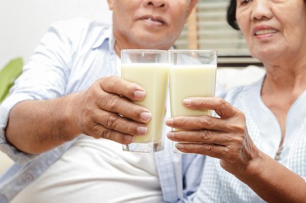 Ein älteres asiatisches paar trinkt kalziumreiche milch, um osteoporose vorzubeugen. Premium Fotos