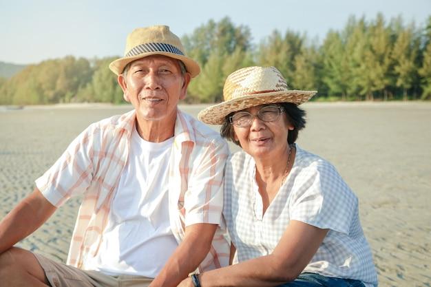 Ein älteres ehepaar ist ein asiat. das sitzen und beobachten des sonnenuntergangs am strand am meer ist glücklich. Premium Fotos