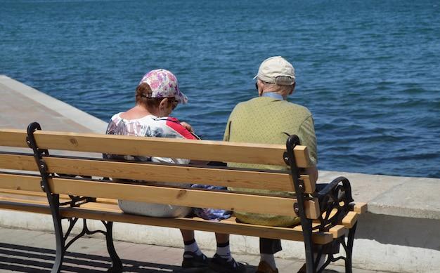 Ein älteres ehepaar schaut auf das meer und sitzt auf einer bank. das konzept der erholung Premium Fotos