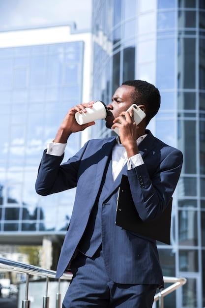 Ein afrikanischer geschäftsmann, der vor dem bürogebäude spricht am trinkenden kaffee des handys steht Kostenlose Fotos