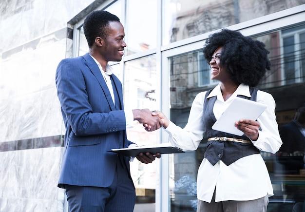 Ein afrikanischer junger geschäftsmann und eine geschäftsfrau, die hände rütteln Kostenlose Fotos