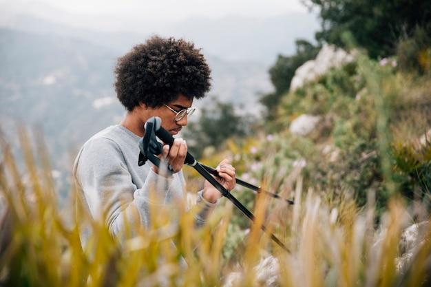 Ein afrikanischer junger männlicher wanderer, der in der hand wanderstock hält Kostenlose Fotos