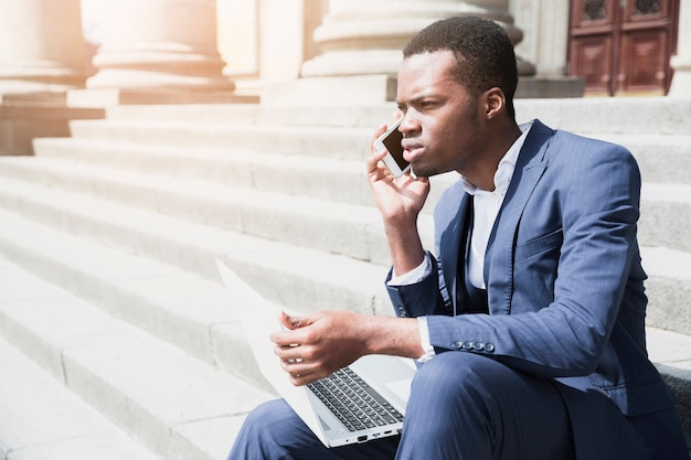 Ein afrikanischer junger mann, der auf dem treppenhaus hält den laptop spricht auf mobile sitzt Kostenlose Fotos