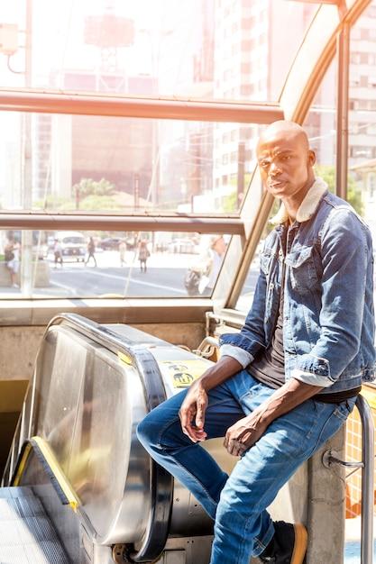 Ein afrikanischer junger mann, der auf der rolltreppe am eingang der u-bahn in der stadt sitzt Kostenlose Fotos