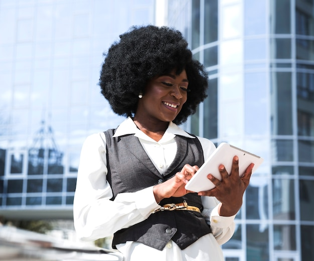 Ein afrikanischer junger mann, der digitale tablette vor unternehmensgebäude verwendet Kostenlose Fotos