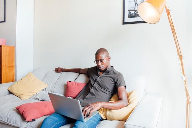 Ein afrikanischer junger mann, der sich zu hause auf sofa unter verwendung des laptops entspannt Kostenlose Fotos