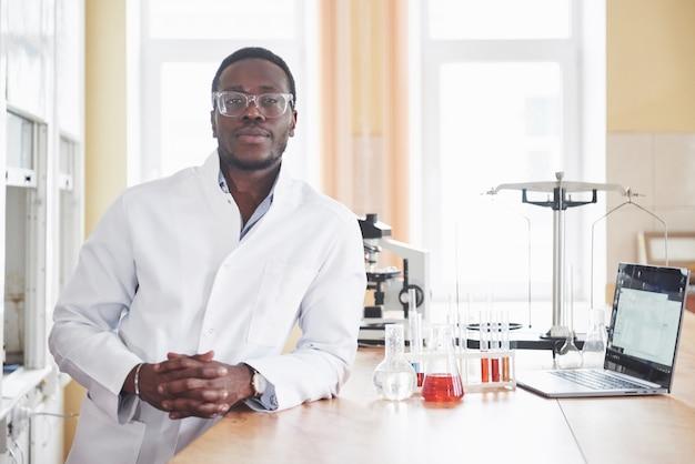 Ein afroamerikanischer arbeiter arbeitet in einem labor und führt experimente durch. Kostenlose Fotos