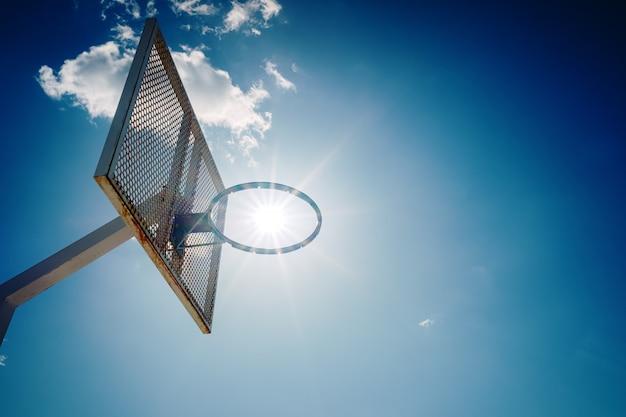 Ein alter basketballkorb außerhalb einer straße mit blauem himmel Premium Fotos
