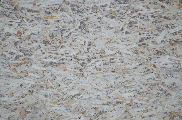 Ein altes orientiertes strangbrett osb, fiberboard hintergrund der beschaffenheit. das blatt besteht aus braunen holzspänen, die zu einem holzfußboden zusammengepresst werden Premium Fotos