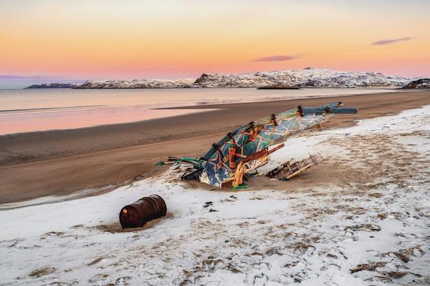 Ein altes rostiges fischerboot, das von einem sturm am ufer verlassen wurde. friedhof der schiffe. kola-halbinsel, teriberka, russland. Premium Fotos