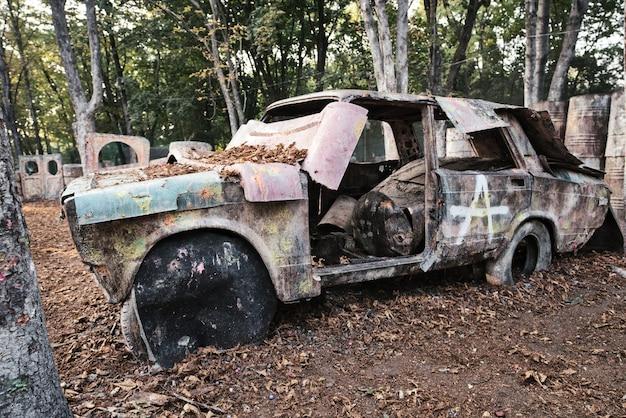 Ein altes rostiges und verlassenes auto auf einer paintballbasis, hinter dem sich vom spiel begeisterte spieler verstecken Premium Fotos
