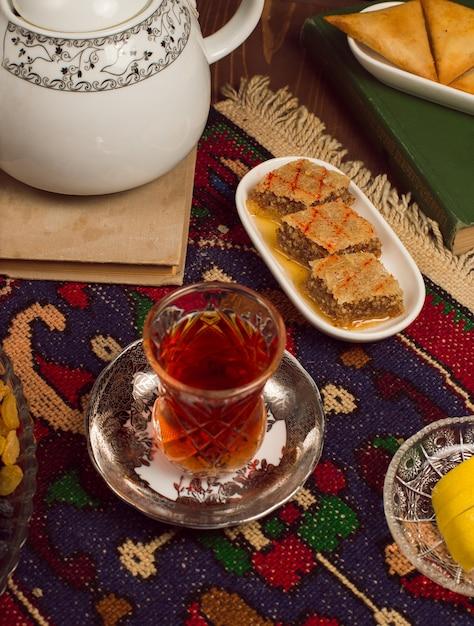 Ein armudu traditionelles glas tee mit bonbons und sheki pakhlavasi auf dunkelheit Kostenlose Fotos