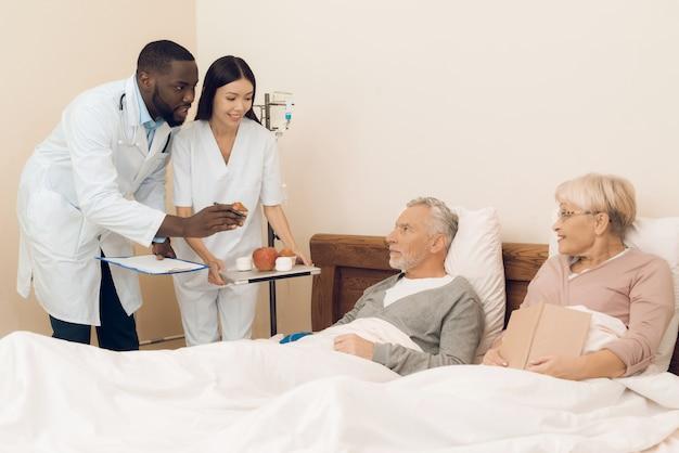 Ein arzt und eine krankenschwester bieten einem älteren ehepaar einen apfel an Premium Fotos