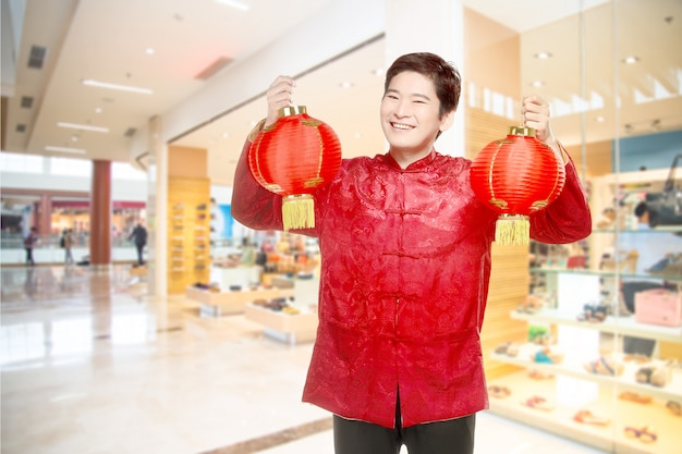 Ein asiatischer chinesischer mann in einem cheongsam kleid, das chinesische laterne anhält Premium Fotos