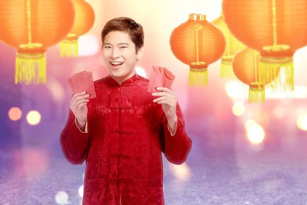 Ein asiatischer chinesischer mann in einem cheongsam kleid, das rote umschläge anhält Premium Fotos