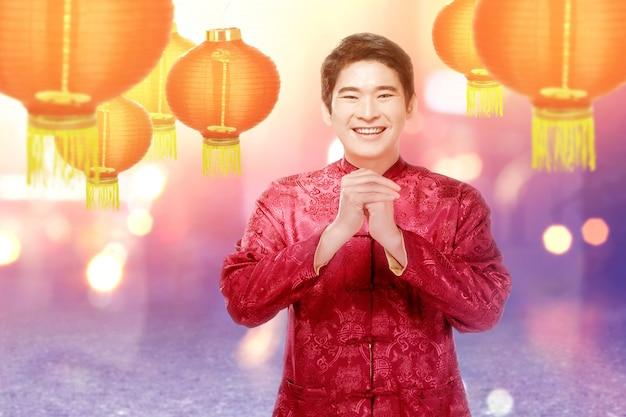 Ein asiatischer chinesischer mann in einem cheongsam kleid mit glückwunschgeste Premium Fotos