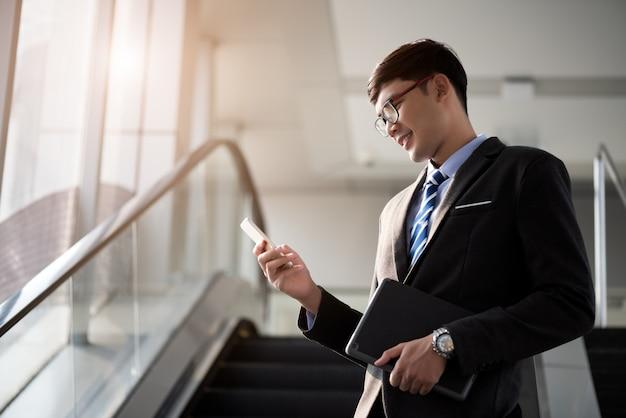 Ein asiatischer geschäftsmann, der sein laptop-tablett, geschäftskonzept hält. Premium Fotos
