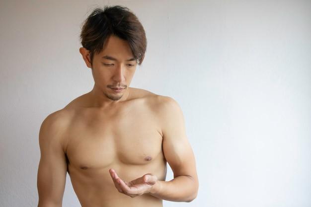 Ein asiatischer mann trägt kein hemd, legt die hände auf die brust. Premium Fotos