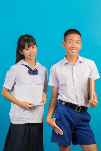 Ein asiatischer student, der ein notizbuch hält, und ein asiatischer männlicher student, der ein grünes brett auf einem blau hält. Kostenlose Fotos
