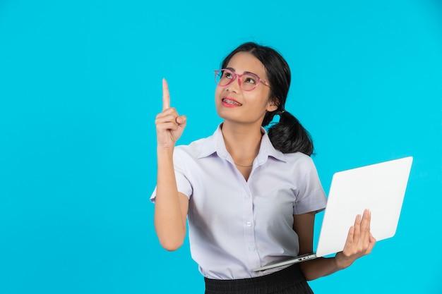 Ein asiatisches kursteilnehmermädchen, das ihr notizbuch auf einem blau anhält. Kostenlose Fotos