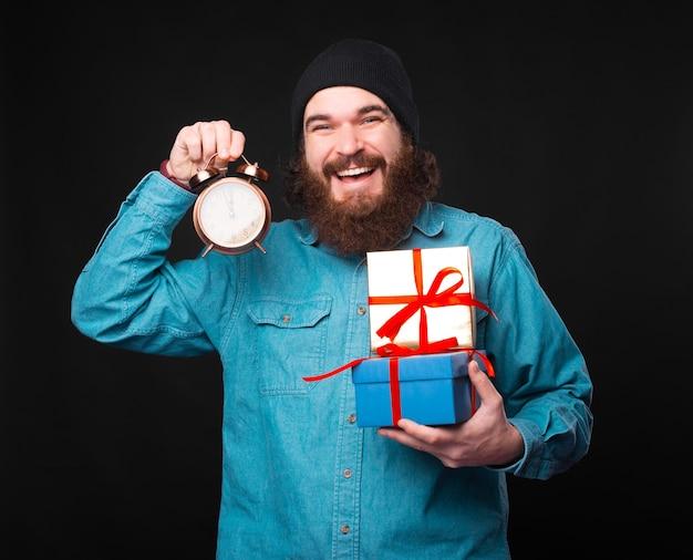 Ein aufgeregter junger bärtiger mann hält einige geschenke und eine kleine uhr in der hand, die zeigt, dass die zeit für sie endet Premium Fotos