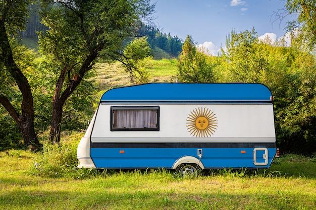 Ein autoanhänger, ein wohnmobil, gemalt in der nationalflagge argentiniens, steht in einem bergpark. Premium Fotos