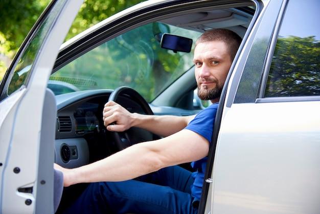 Ein bärtiger junger mann sitzt in einem auto mit einer offenen tür. Premium Fotos