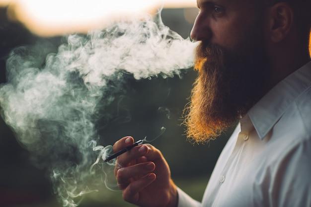 Ein bärtiger mann raucht eine zigarette gegen den sonnenuntergang. Premium Fotos