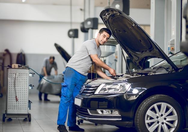 Ein bankier, der den motor eines autos repariert Kostenlose Fotos