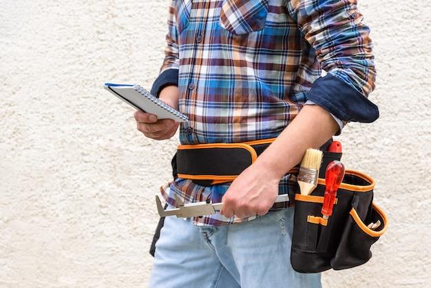 Ein bauarbeiter in einem blau karierten hemd mit werkzeugen im gürtel. der arbeiter hält einen notizblock und ein messwerkzeug in der hand. Premium Fotos