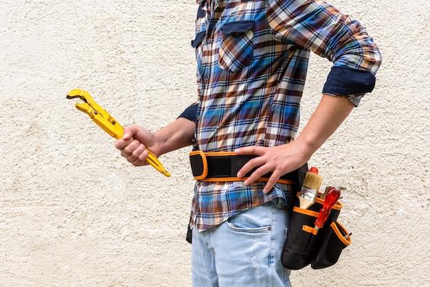 Ein bauarbeiter in einem blau karierten hemd mit werkzeugen im gürtel hält einen gelben schraubenschlüssel in den händen. Premium Fotos
