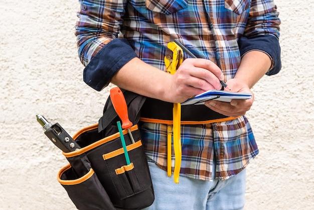 Ein bauarbeiter in einem blau karierten hemd mit werkzeugen im gürtel macht eine notiz mit einem bleistift in einem notizbuch. Premium Fotos