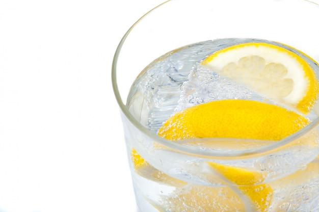 Ein becherglas mit kristallklarem wasser, zitronen- und eiswürfeln. Premium Fotos