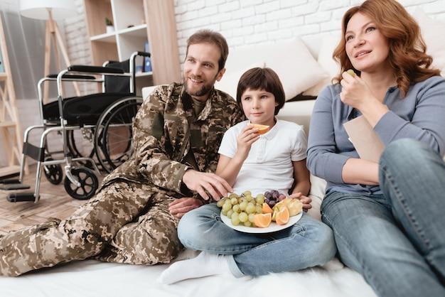 Ein behinderter vater in militäruniform isst früchte. Premium Fotos